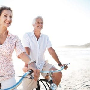 A senior couple riding their bikes together on the beach